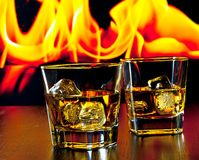 Two glasses of whiskey with ice cubes in front of the flame Royalty Free Stock Image