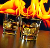 Two glasses of whiskey with ice cubes in front of the flame Stock Photography