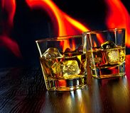 Two glasses of whiskey with ice cubes in front of the flame Stock Photo