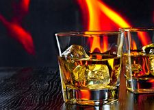 Two glasses of whiskey with ice cubes in front of the flame Royalty Free Stock Photo