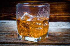 Two glasses of whiskey with ice cubes served on wooden planks. Vintage countertop with highlight and a glass of hard liquor delici Stock Images
