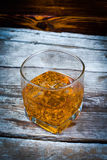 Two glasses of whiskey with ice cubes served on wooden planks. Vintage countertop with highlight and a glass of hard liquor delici Royalty Free Stock Photography