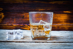 Two glasses of whiskey with ice cubes served on wooden planks. Vintage countertop with highlight and a glass of hard liquor delici royalty free stock photos