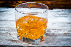Two glasses of whiskey with ice cubes served on wooden planks. Vintage countertop with highlight and a glass of hard liquor delici royalty free stock images