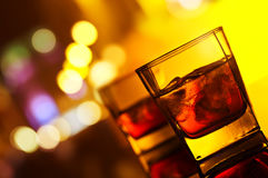Two glasses of whiskey with ice. Whiskey with ice on a glass table in bar on a background of night city Royalty Free Stock Image
