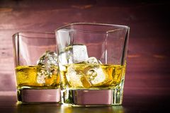 Two glasses of whiskey with ice on old wood table Stock Photo