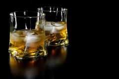 Two glasses of whiskey with ice with space for text Stock Photography