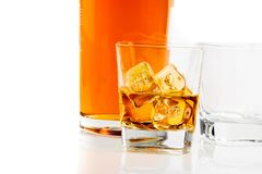 Two glasses of whiskey near bottle on white background with reflection Stock Image