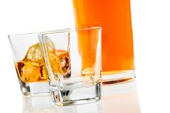 Two glasses of whiskey near bottle on white background with reflection Royalty Free Stock Photo