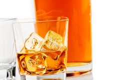 Two glasses of whiskey near bottle on white background with reflection Royalty Free Stock Images