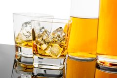 Two glasses of whiskey near bottles on black background with reflection Stock Photos