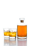 Two glasses of whiskey on the rocks, with a whiskey bottle in white background Stock Photos