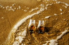 Two glasses of whiskey single malt on the sand washed by the waves, a glass of tasting, relax on the beach. Vacation royalty free stock photos