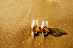 Two glasses of whiskey single malt on the sand washed by the waves, a glass of tasting, relax on the beach. Vacation royalty free stock photography