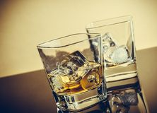 Two glasses of whiskey on table with reflection, warm atmosphere Stock Image