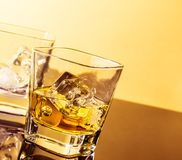 Two glasses of whiskey on table with reflection, warm atmosphere Royalty Free Stock Photos