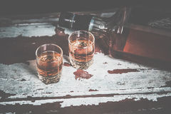 Two glasses of whiskey vintage photo, a bottle on the bar Stock Photo