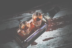 Two glasses of whiskey vintage photo, a bottle on the bar Stock Photos