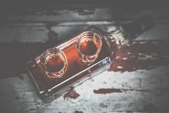 Two glasses of whiskey vintage photo, a bottle on the bar Stock Image