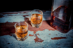 Two glasses of whiskey vintage photo, a bottle on the bar Royalty Free Stock Photos