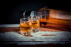 Two glasses of whiskey vintage photo, a bottle on the bar Royalty Free Stock Photo