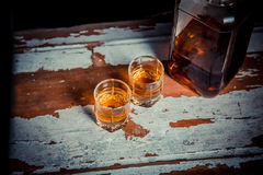 Two glasses of whiskey vintage photo, a bottle on the bar Stock Images