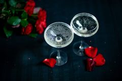 Two glasses with white champagne and petals of red roses on the black background stock images