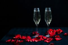 Two glasses with white champagne and petals of red roses on the black background. Valentines day romantic concept. 8 March and Mothers Day concept royalty free stock image