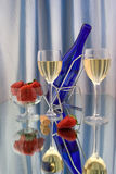 Two glasses of white wine. With dark blue bottle and strawberries Stock Photo