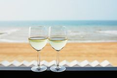 Two glasses of white wine with Atlantic coast beach in background. Normandy, France royalty free stock images