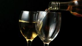 Two glasses of white wine being poured stock footage