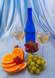 Two glasses of white wine and blue bottle with oranges Royalty Free Stock Images