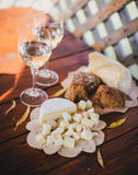 Two glasses of white wine with cheese and bread on a table Royalty Free Stock Photo