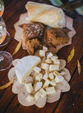 Two glasses of white wine with cheese and bread on a table Royalty Free Stock Images