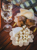 Two glasses of white wine with cheese and bread on a table Stock Photo
