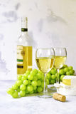 Two glasses of white wine,cheese and grapes. Stock Photo