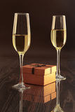 Two glasses with white wine and gift box on mirror table. Celebrities composition. Stock Photos