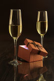 Two glasses with white wine and gift box on mirror table. Celebrities composition. Stock Photography