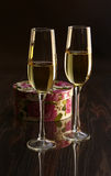 Two glasses with white wine and gift box on mirror table. Celebrities composition. Your text here. Royalty Free Stock Photos