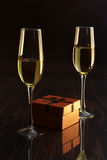 Two glasses with white wine and gift box on mirror table. Celebrities composition. Your text here. Stock Images