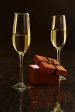 Two glasses with white wine and gift box on mirror table. Celebrities composition. Your text here. Stock Image