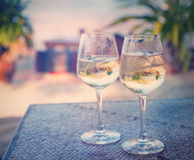 Two glasses of white wine with ice on a table at the beach cafe Royalty Free Stock Photos