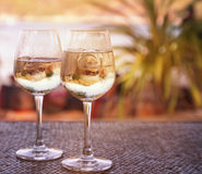 Two glasses of white wine with ice on a table at the beach cafe Stock Photos