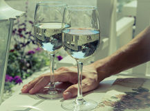 Two glasses of white wine with man hand in the background Stock Photography