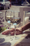 Two glasses of white wine with man hand in the background Royalty Free Stock Images