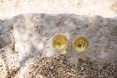 Two glasses of white wine at pebble beach stock photography