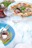 Two glasses of white wine. Pizza with prosciutto and olives. Green salad. Servian lunch, on a light background with punctuated royalty free stock photos