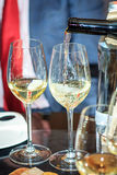 Two glasses of white wine, the process of pouring wine Stock Photo