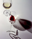 Two glasses of white wine and red wine. On a white shiny background Stock Photography