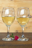 Two glasses of white wine and a rose Stock Photos